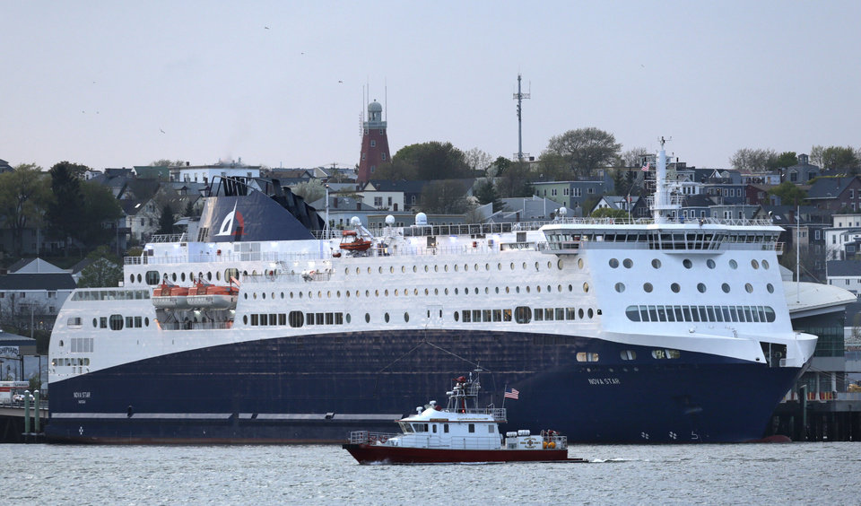 Photo - The 528-foot, $165 million Nova Star ferry dwarfs the city of Portland's fire boat as it prepares to leave Portland, Maine,Thursday night on its first commercial run to Yarmouth, Nova Scotia, Canada, Thursday, May 15, 2014. The ship has 162 cabins that range from $99 to $249 a night in the summer. (Photo/Robert F. Bukaty)