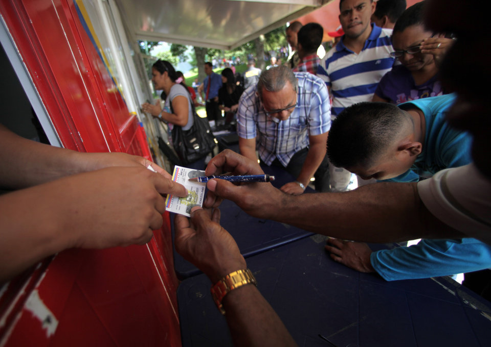 Residents get regular Identification Cards they will need to be allowed to vote, one day before election day, in Caracas, Venezuela, Saturday, Oct. 6, 2012. Venezuela's President is running for a third term in office against opposition candidate Henrique Capriles in presidential elections on Oct. 7.(AP Photo/Fernando Llano)