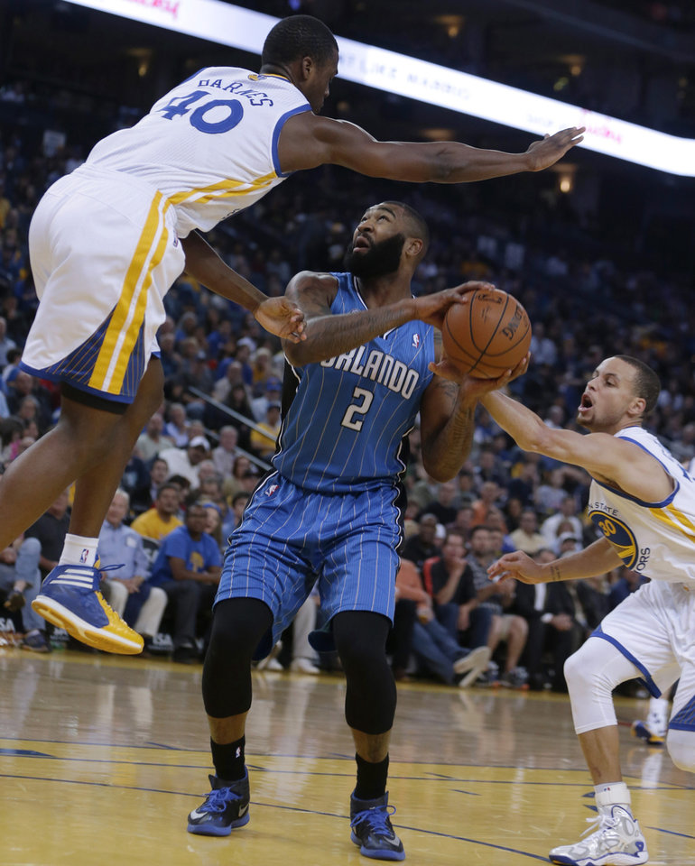 Photo - Orlando Magic forward Kyle O'Quinn, center, attempts a shot between Golden State Warriors' Harrison Barnes, left, and Stephen Curry during the first half of an NBA basketball game Tuesday, March 18, 2014, in Oakland, Calif. (AP Photo/Ben Margot)