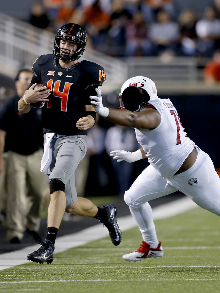 Photo - Oklahoma State's Taylor Cornelius (14) is pushed out of bounds by South Alabama's Sean Brown (74) in the third quarter during a college football game between Oklahoma State (OSU) and South Alabama at Boone Pickens Stadium in Stillwater, Okla., Saturday, Sept. 8, 2018. Photo by Sarah Phipps, The Oklahoman