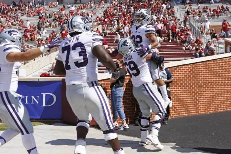 Photo -  Kansas State's Deuce Vaughn (22) and Noah Johnson (69) celebrate after Vaughn's game-tying touchdown late ini the fourth quarter Saturday in a 38-35 win at OU. [Bryan Terry/The Oklahoman]