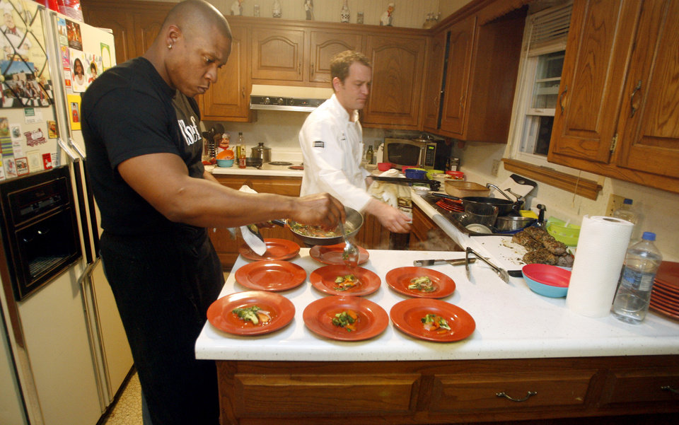 Photo - Top Chef contestant Tre Wilcox and Deep Fork executive chef Joshua Richardson plate dinner for Cat Taylor and her friends, Sunday, Nov. 30, 2008, in Oklahoma City, Okla. STAFF PHOTO BY SARAH PHIPPS  ORG XMIT: KOD