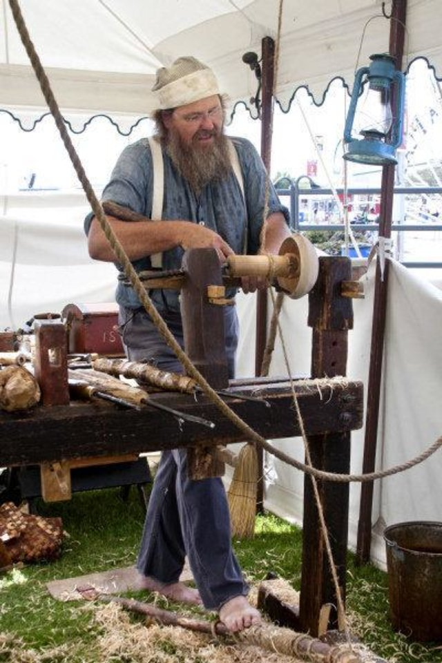 Photo - Roger Abrahamson from Minneapolis, Minn., uses a spring pole lathe and a hook tool to create a wooden bowl out of sycamore using the same wood turning techniques that tradesmen did 100 years ago at the Oklahoma State Fair. Photo by Lillie-Beth Brinkman, The Oklahoman  Lillie-Beth Brinkman