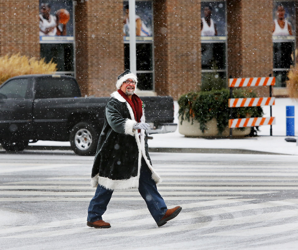 Bill Long, a local arborist, smiles as he leaves the Cox Convention Center after volunteering at the Red Andrews Dinner. Long said he enjoyed the morning snowfall and to celebrate the white Christmas, he dressed in a Santa suit with red and green bows attached to his coat.  A white Christmas in downtown Oklahoma City, Dec. 25, 2012. Looking west down NW 4th from Harvey.   Photo by Jim Beckel, The Oklahoman