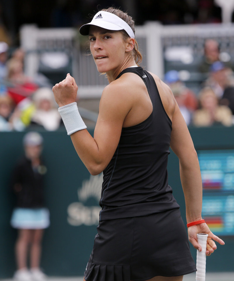 Photo - Andrea Petkovic, of Germany, clenches her fist after a point in the final against Jana Cepelova, of Slovakia, during the Family Circle Cup tennis tournament in Charleston, S.C., Sunday, April 6, 2014. Petkovic won 7-5, 2-6. (AP Photo/Mic Smith)