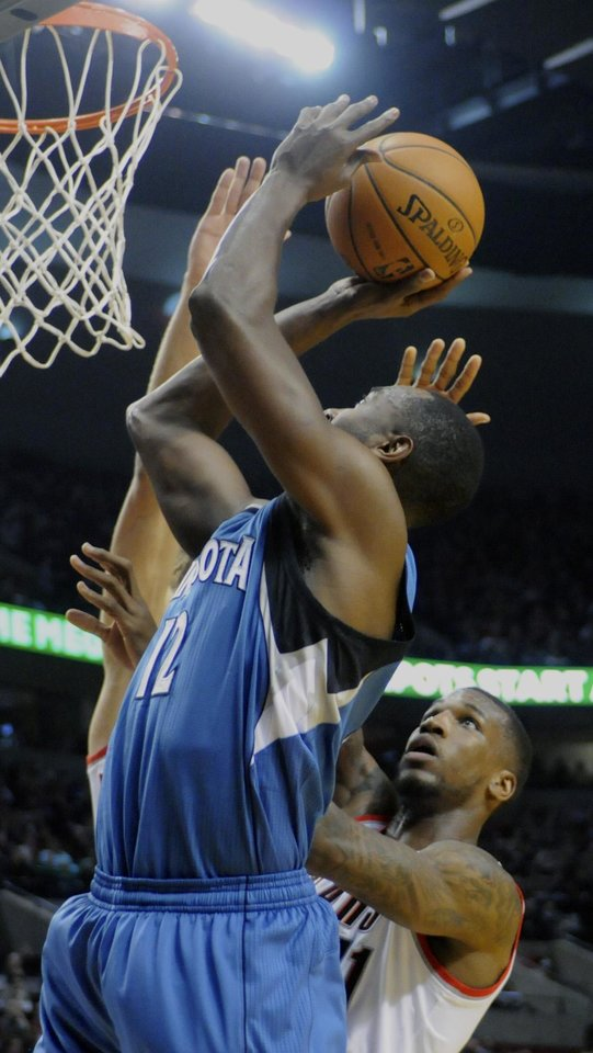 Minnesota Timberwolves' Luc Mbah a Moute (12) shoots against Portland Trail Blazers' Thomas Robinson (41) during the first half of an NBA basketball game in Portland, Ore., Sunday Feb. 23, 2014. (AP Photo/Greg Wahl-Stephens)