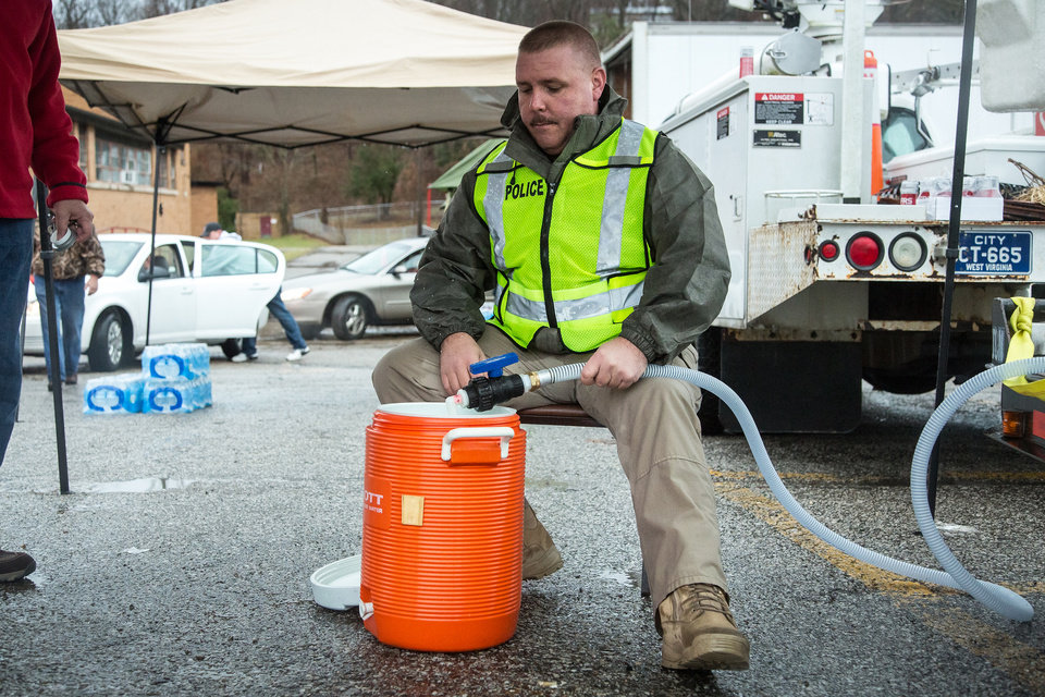Photo - Nitro, WV Chief of Police Brian Oxley helps distribute water to local residents Saturday, Jan. 11, 2014 following the chemical spill on Thursday in Charleston, W.V. About 300,000 people in nine counties entered their third day Saturday without being able to drink, bathe in, or wash dishes or clothes with their tap water after a foaming agent escaped the Freedom Industries plant in Charleston and seeped into the Elk River.  (AP Photo Michael Switzer)