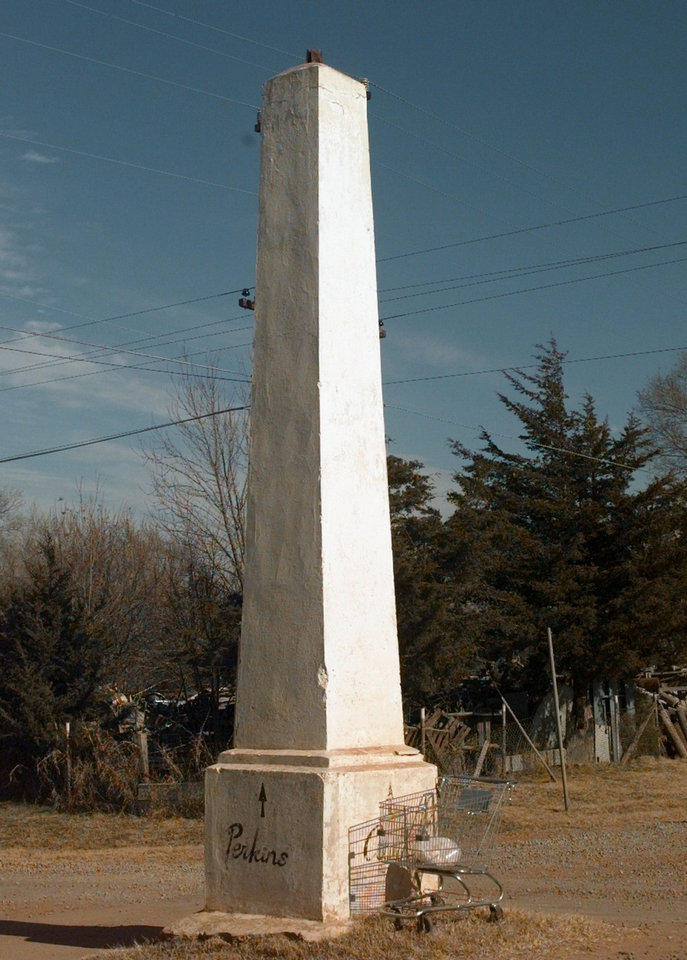 "Photo - The Indian Meridian Obelisk It marks the Ozark trail, which settlers traveled more than 100 years ago, and is the point in Oklahoma from which all distances are measured. In the years since this photograph was taken, the paint pointing the way to Perkins has faded or chipped away.  The battered obelisk stands smack dab in the middle of the Washington and Logan intersection. And it has stood there since 1870.  Perhaps 25 feet tall, its once-white surface is pocked and chipped, a casualty of time and innumerable car crashes. It's unlit, you see, and many a driver, startled to see it looming out of the rural darkness, has collided with history.   ""They've bumped it and bumped it,"" an observer once told The Oklahoman, ""but they've never moved it.""  The marker is worth seeing just for its incongruence. Photo By Paul Hellstern, The Oklahoman Archives"