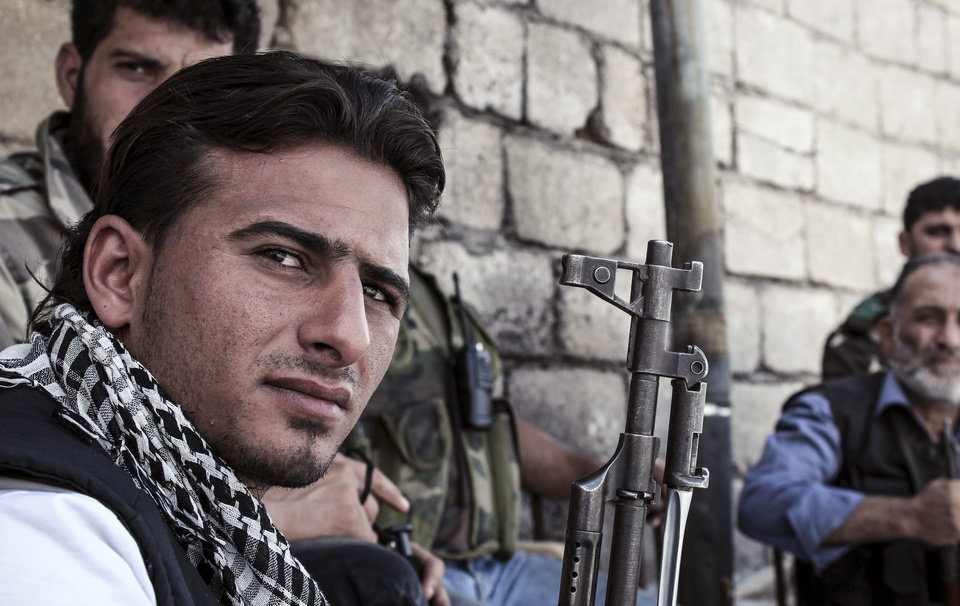 Photo -   In this Tuesday, Oct. 30, 2012 photo, a Syrian rebel takes a break during fierce fighting in the town of Harem in Idlib province, Syria. Despite two weeks of attacking a Roman-era citadel in which pro-Assad militia were dug in, the rebels failed to secure the town. (AP Photo/Mustafa Karali)