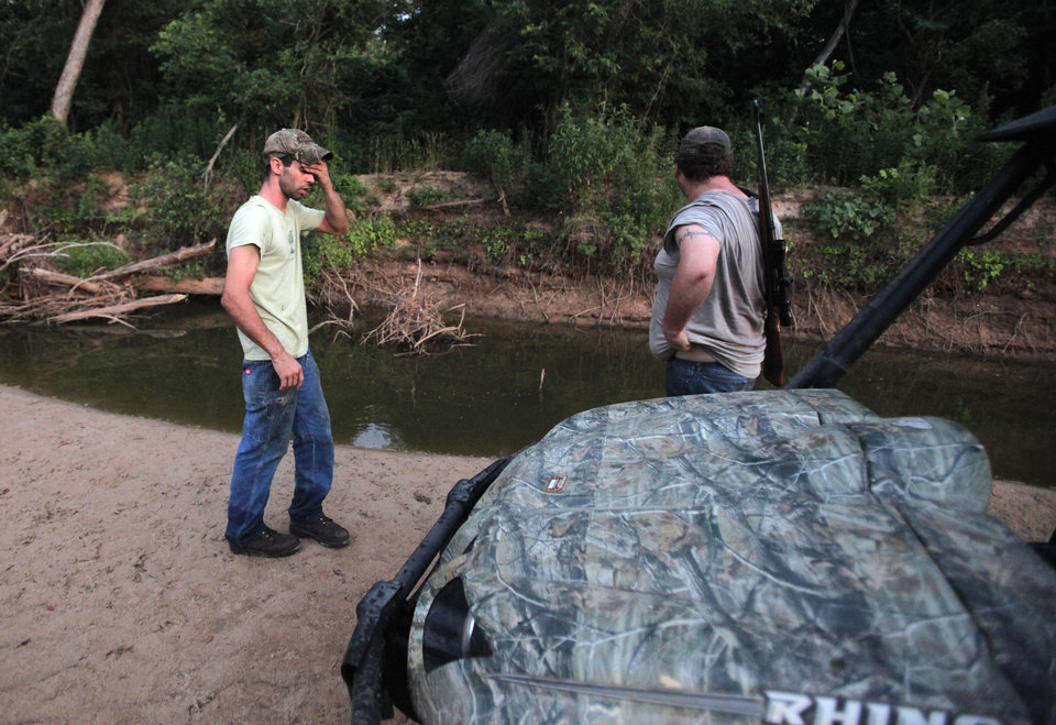 Johnny Heskett and Josh Kinsey look for places to place hog traps during a hunting trip near Indianola, Okla., Friday, July 6, 2012.  Photo by Garett Fisbeck, The Oklahoman
