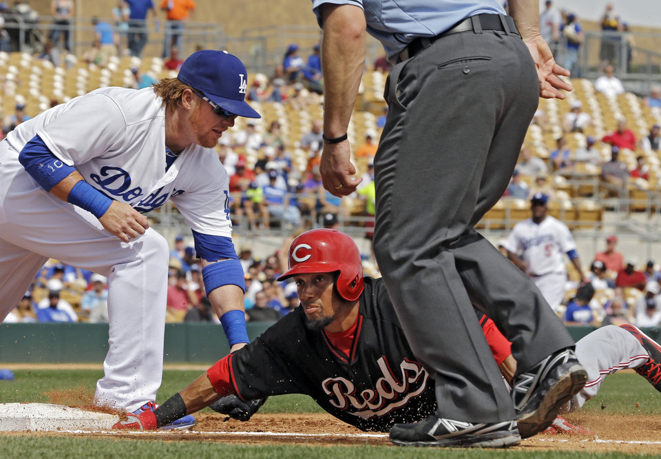 Photo - Cincinnati Reds' Billy Hamilton, center, dives safely back to first ahead of there tag by Los Angeles Dodgers first baseman Justin Turner, left, on a pickoff-attempt in the third inning of a spring exhibition baseball game on Thursday, March 13, 2014, in Glendale, Ariz. (AP Photo/Mark Duncan)