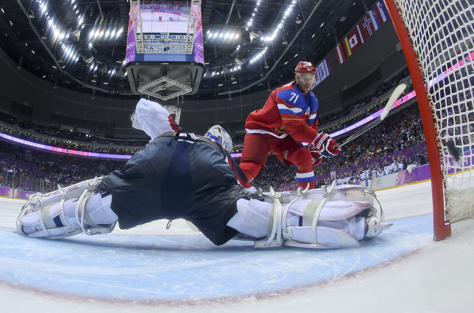 Photo - Russia forward Ilya Kovalchuk flips the puck past Slovakia goaltender Jan Laco to score in a shootout during overtime of a men's ice hockey game at the 2014 Winter Olympics, Sunday Feb. 16, 2014, in Sochi, Russia. The shot gave Russia a 1-0 win. (AP Photo/Bruce Bennett, Pool)