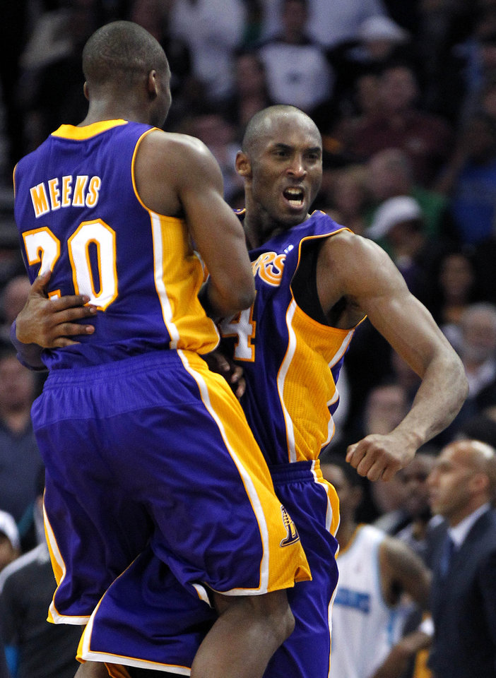 Photo - Los Angeles Lakers guard Kobe Bryant celebrates with guard Jodie Meeks (20) after scoring in the final minute of an NBA basketball game against the New Orleans Hornets in New Orleans, Wednesday, March 6, 2013. The Lakers won 108-102. (AP Photo/Gerald Herbert)