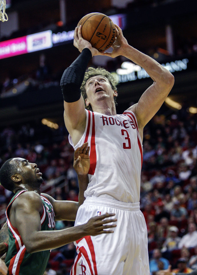 Photo - Houston Rockets center Omer Asik (3) is fouled by Milwaukee Bucks forward Luc Richard Mbah a Moute (12) during the second half of an NBA basketball game, Wednesday, Feb. 27, 2013 in Houston. Milwaukee won 110-107. (AP Photo/Bob Levey)