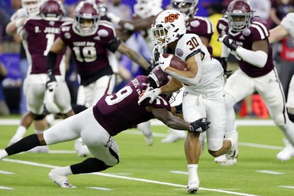 Photo -  Oklahoma State running back Chuba Hubbard (30) is caught by Texas A&M defensive back Leon O'Neal Jr. (9) during the first half Friday in Houston. [AP Photo/Michael Wyke]