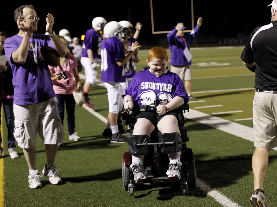 Photo - Keegan Erbst reacts beside his father, Scott, during a Sequoyah Middle School football game, Thursday, September 27, 2012. Keegan, who has muscular dystrophy and is confined to a wheelchair, got involved with the team after players Lucas Coker, Colton James, and Parker Tumleson, suggested it to the coach.  Photo by Bryan Terry, The Oklahoman