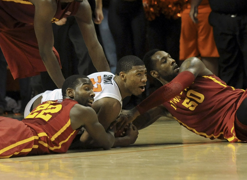 Photo - Iowa State's Dustin Hogue (22) and DeAndre Kane (50) tie up Oklahoma State's Marcus Smart (33) to take the game into a third overtime in an NCAA college basketball game in Stillwater, Okla., Monday, Feb. 3, 2014. Smart scored 20 points in the 97-98 loss to Iowa State. (AP Photo/Brody Schmidt)