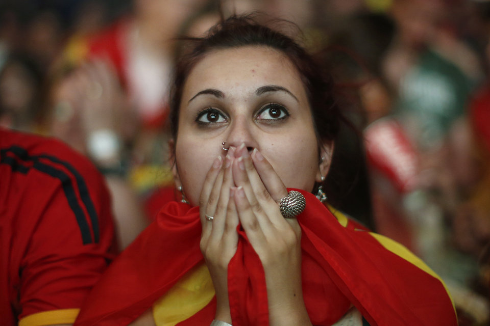 Photo - A Spanish soccer fan covers her face as she watches on a giant display a World Cup soccer match between Spain and Chile, in Madrid, Spain, Wednesday, June 18, 2014. (AP Photo/Andres Kudacki)
