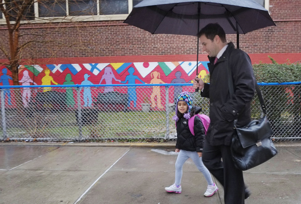 Photo - Matthew Mosca takes his daughter, Ella, to her kindergarten class at Public School 33, Wednesday, Jan. 16, 2013 in New York. Mosca said his 5-year-old usually takes the bus from their home on Manhattan's East Side, but took a taxi today.  More than 8,000 New York City school bus drivers and aides went on strike over job protection Wednesday morning, leaving some 152,000 students trying to find other ways to get to school. (AP Photo/Mark Lennihan)