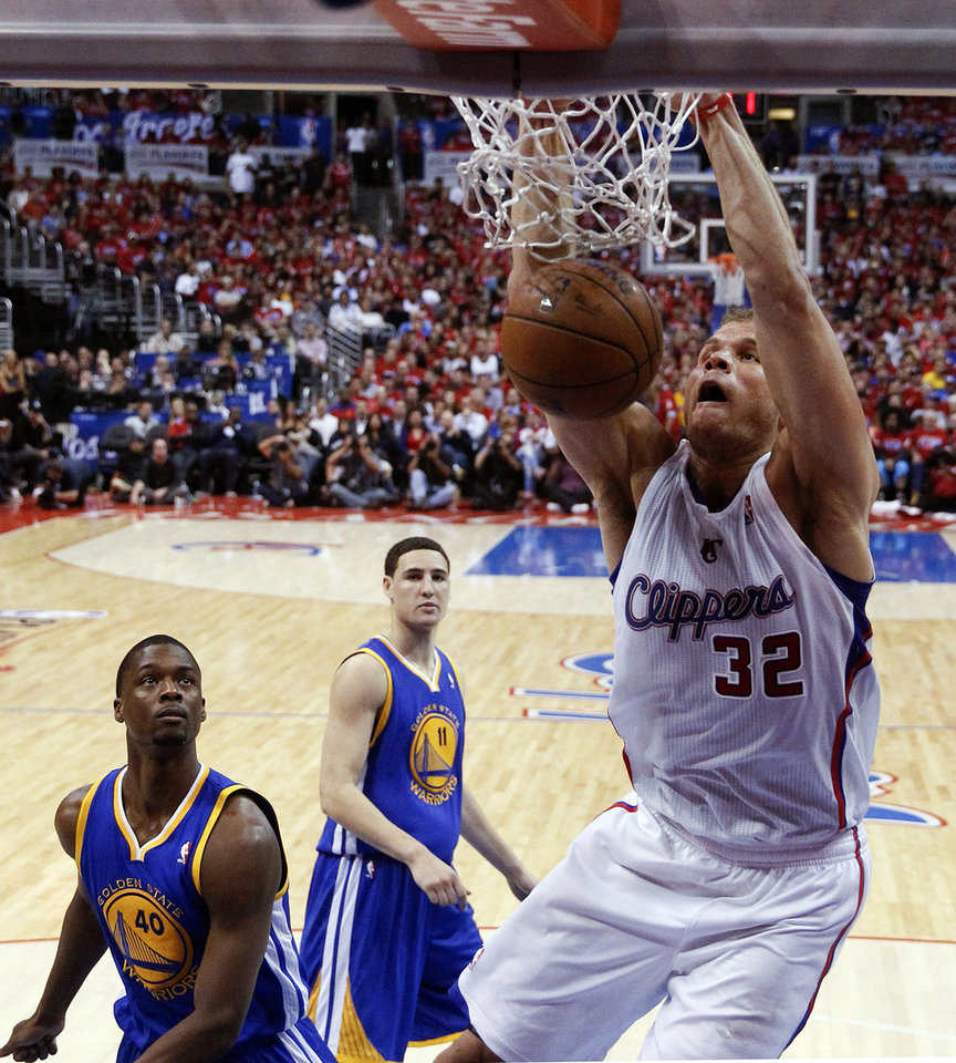 Photo - Los Angeles Clippers forward Blake Griffin, right, dunks as Golden State Warriors forward Harrison Barnes, left, and Klay Thompson look on during the second half in Game 2 of an opening-round NBA basketball playoff series in Los Angeles, Monday, April 21, 2014. (AP Photo/Chris Carlson)