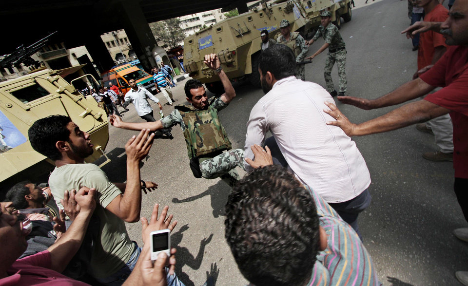 Photo -   Protesters clash with Egyptian military outside the Defense Ministry in Cairo, Egypt, Wednesday, May 2, 2012. Suspected supporters of Egypt's military rulers attacked predominantly Islamist anti-government protesters outside the Defense Ministry in Cairo Wednesday, setting off clashes that left more than ten people dead as political tensions rise three weeks before crucial presidential elections. (AP Photo)