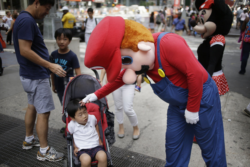 "Photo - A person dressed as Mario pats a child on the head in Times Square on Monday, July 28, 2014 in New York. New York City Mayor Bill de Blasio said Monday that he believes the people wearing character costumes in Times Square should be licensed and regulated. Dozens of people dressed as kids' favorites like Elmo, Cookie Monster and Batman stand near 42nd Street and pose for photos with tourists in exchange for money. De Blasio said the practice has ""gone too far.""  A man dressed as Spider-man was arrested Saturday, July 28, 2014, after punching a police officer who told him to stop harassing tourists.  The City Council is working on legislation that would require the characters to get a city-approved license.  (AP Photo/Seth Wenig)"