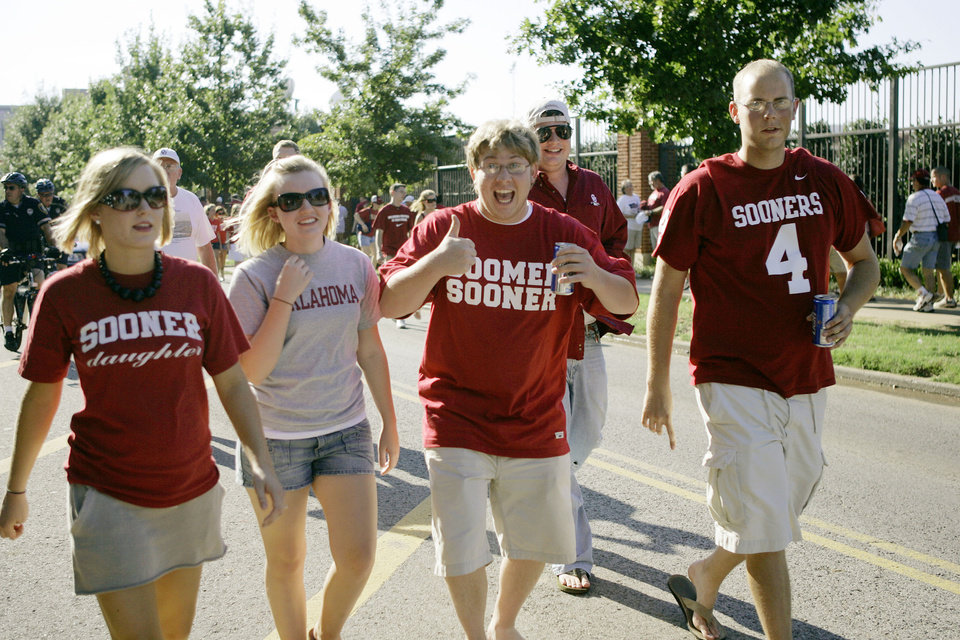 Photo - Oklahoma Sooners fans Austin Dejohn gives aa thumbs up as he, Courtney Bucklin, center left, make their way  with friends to the stadium before the University of Oklahoma Sooners (OU) college football game against the University of North Texas Mean Green (UNT) at the Gaylord Family - Oklahoma Memorial Stadium, on Saturday, Sept. 1, 2007, in Norman, Okla.