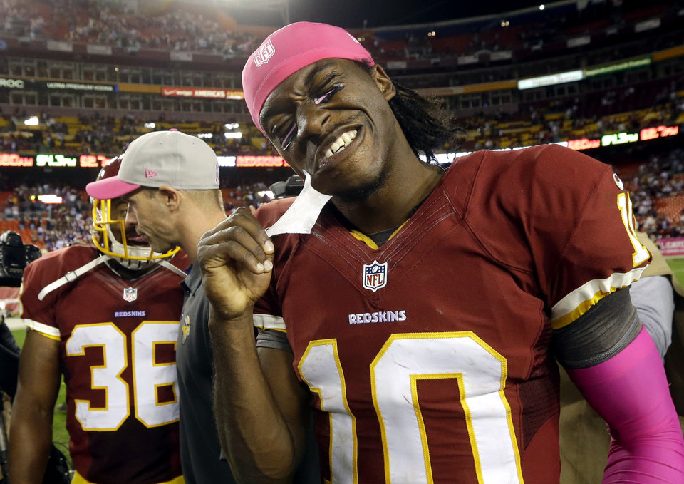 Photo -   Washington Redskins quarterback Robert Griffin III (10) pulls tape off his chin after an NFL football game against the Minnesota Vikings, Sunday, Oct. 14, 2012, in Landover, Md. The Redskins won 38-26. (AP Photo/Pablo Martinez Monsivais)