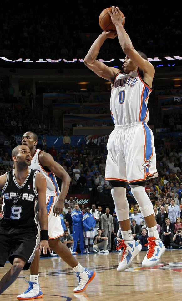 Photo - Oklahoma City's Russell Westbrook (0) shoots a jumper near Serge Ibaka (9) and San Antonio's Tony Parker (9) during the NBA basketball game between the Oklahoma City Thunder and the San Antonio Spurs at Chesapeake Energy Arena in Oklahoma City, Friday, March 16, 2012. San Antonio won, 114-105. Photo by Nate Billings, The Oklahoman