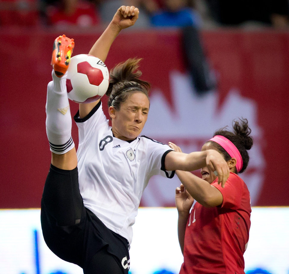 Photo - Germany's Nadine Kebler, left, tries to get her foot on the ball but misses while under pressure from Canada's Desiree Scott during the second half of an international women's soccer game in Vancouver, British Columbia on Wednesday, June 18, 2014.  (AP Photo/The Canadian Press, Darryl Dyck)