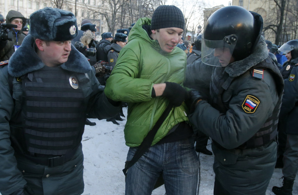 Photo - Police officers detain an opposition activist during an unauthorized rally in Lubyanka Square in Moscow, Russia, Saturday, Dec. 15, 2012. Thousands of opposition supporters gathered Saturday in central Moscow for an unauthorized rally to mark a year of a wave of massive protests against Vladimir Putin and the government. Several prominent opposition figures were detained in the course of the gathering, which was not sanctioned by authorities. (AP Photo/Misha Japaridze)