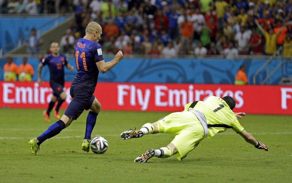 Photo - Netherlands' Arjen Robben goes around Spain's goalkeeper Iker Casillas to score his side's fifth goal during the second half of the group B World Cup soccer match between Spain and the Netherlands at the Arena Ponte Nova in Salvador, Brazil, Friday, June 13, 2014.  (AP Photo/Natacha Pisarenko)