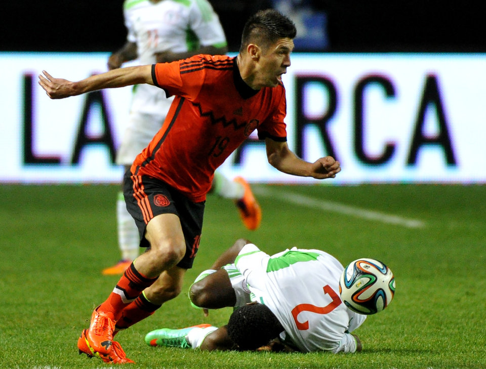 Photo - Nigeria's Godfrey Oboabona (2) grabs his injured knee and falls to the turf as Mexico's Oribe Peralta (19) dribbles past during the first half of an international friendly soccer match Wednesday, March 5, 2014, in Atlanta. (AP Photo/David Tulis)