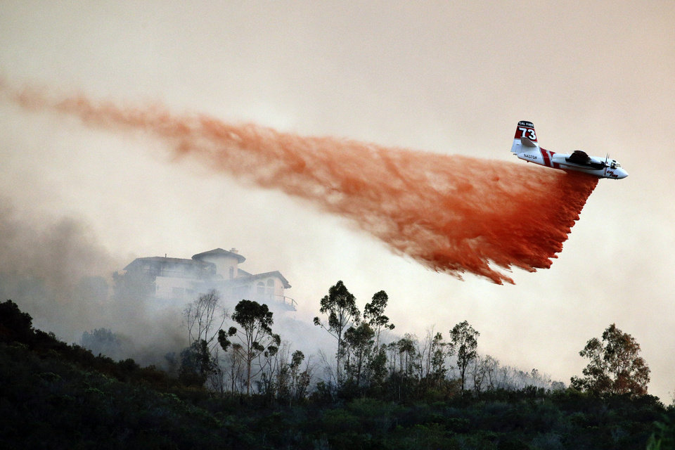 Photo - A plane drops fire retardant over a hot spot on Wednesday, May 14, 2014, in San Marcos, Calif. Wednesday, May 14, 2014, in San Marcos, Calif. Flames engulfed suburban homes and shot up along canyon ridges in one of the worst of several blazes that broke out Wednesday in Southern California during a second day of a sweltering heat wave, taxing fire crews who fear the scattered fires mark only the beginning of a long wildfire season. (AP Photo)