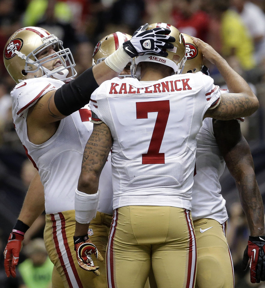 Photo - San Francisco 49ers quarterback Colin Kaepernick (7) celebrates his touchdown pass in the second half of an NFL football game against the New Orleans Saints in New Orleans, Sunday, Nov. 17, 2013. (AP Photo/Dave Martin)