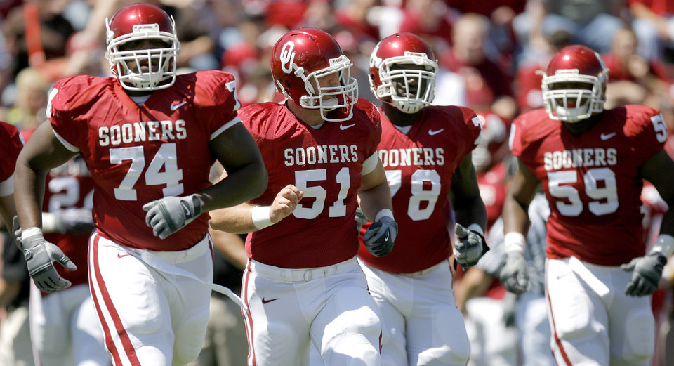 Photo - OU's Brian Simmons, left, Brian Lepak, Alex Williams, and Donald Stephenson walk towards the ball before a play  during Oklahoma's Red-White football game at The Gaylord Family - Oklahoma Memorial Stadiumin Norman, Okla., Saturday, April 11, 2009. Photo by Bryan Terry, The Oklahoman