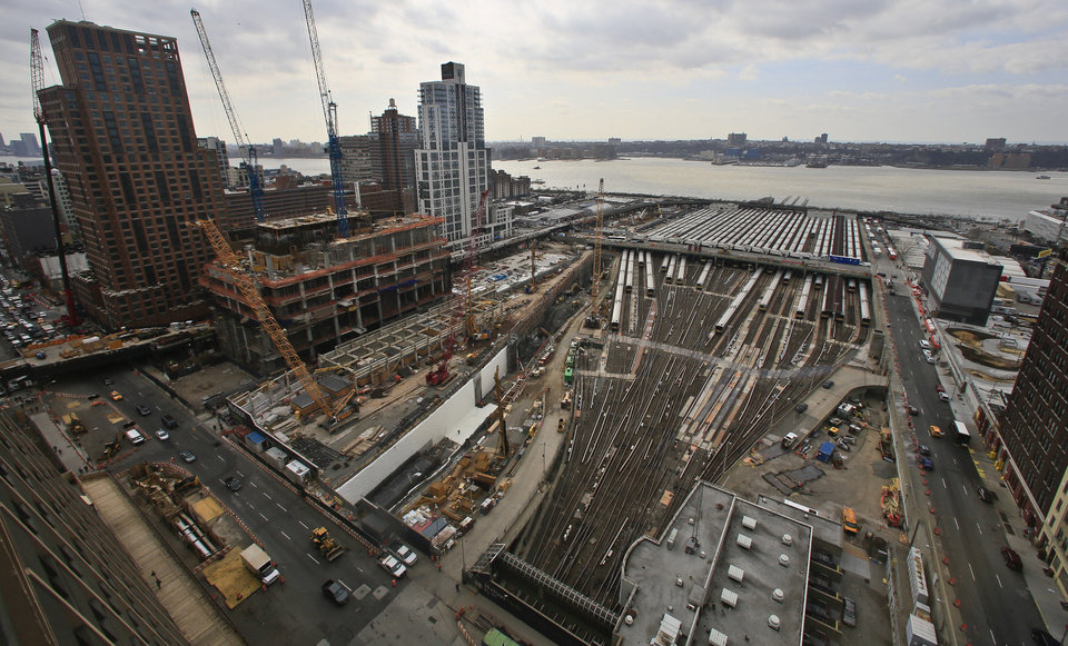 Photo - This photo of the Hudson Yards project site shows ongoing construction of skyscrapers and parked Long Island Rail Road trains, Thursday April 17, 2014 in New York. The $15 billion Hudson Yards will fill 28 acres between the Hudson River and Tenth Avenue with six skyscrapers after completely covering the train yards with a platform foundation. (AP Photo/Bebeto Matthews)