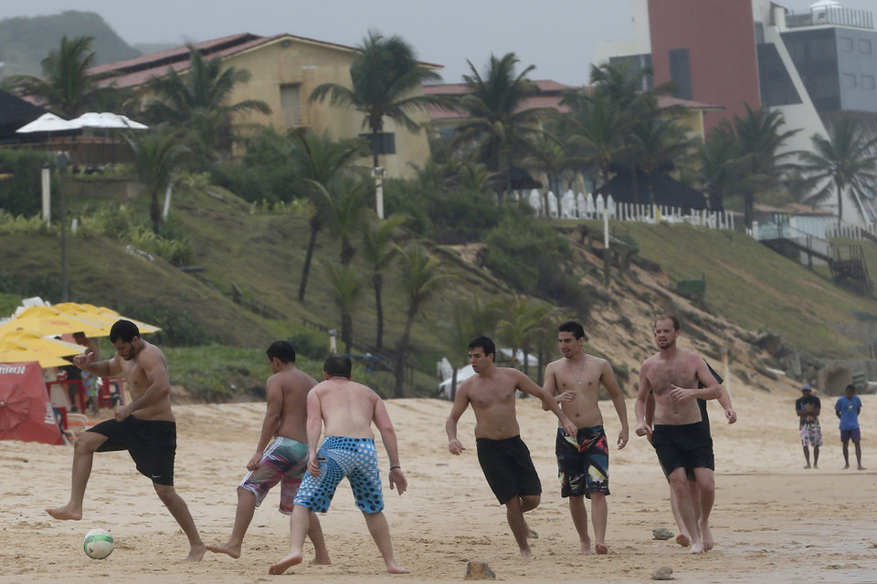Photo - Tourists play soccer during a rainy day at the beach in Natal, Brazil, Saturday, June 14, 2014. Natal is one of 12 cities hosting games during the 2014 World Cup soccer tournament. (AP Photo/Julio Cortez)