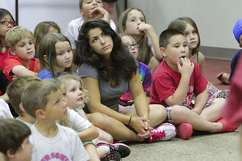 Photo - Children watch the Rhythmically Speaking acting troupe perform Monday at the Norman Public Library as part of the library's Summer Reading Program. PHOTOS BY DAVID MCDANIEL, THE OKLAHOMAN