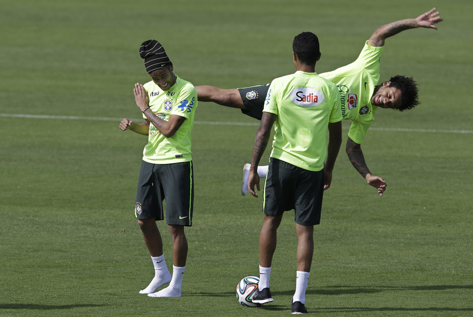 Photo - Brazil's Mrcelo, behind right, jokes with teammate Neymar, left, during a training session at the Granja Comary training center in Teresopolis, Brazil, Saturday, June 14, 2014. Brazil plays in group A at the 2014 soccer World Cup. (AP Photo/Andre Penner)