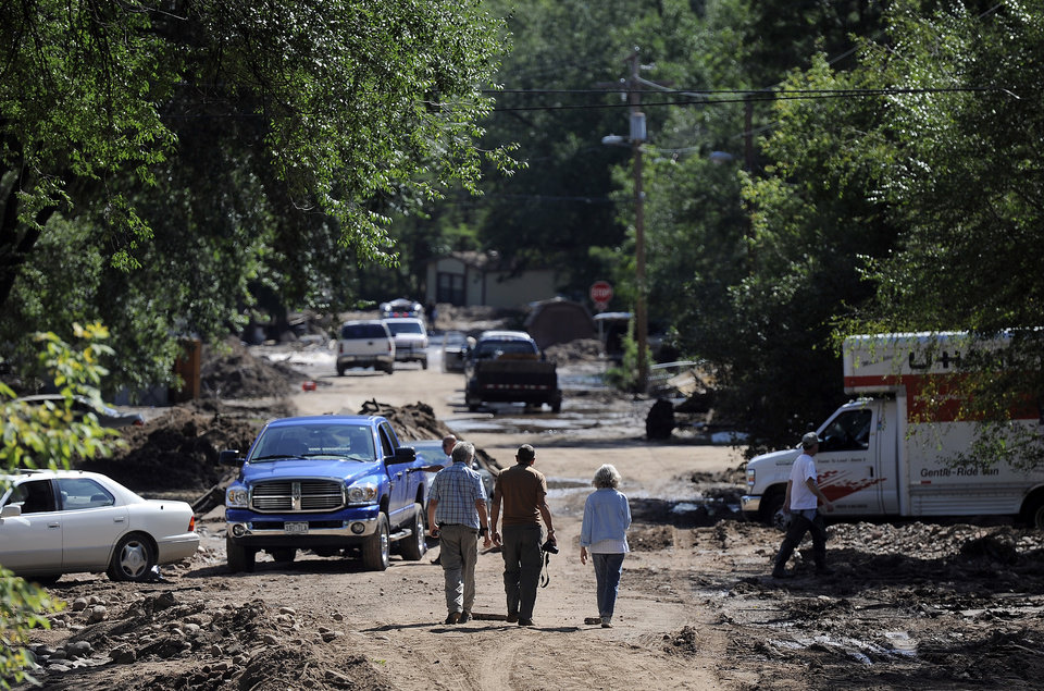 Photo - People walk through a severely flooded neighborhood in Lyons, Colo., on Thursday, Sept. 19, 2013. Residents displaced by last week's flooding in the Colorado canyon town were allowed past National Guard roadblocks Thursday to find a scene of tangled power lines, downed utility poles, mud-caked homes and vehicles, and work crews furiously clearing debris and trying to restore power, water and sewer service.   (AP Photo/Chris Schneider)