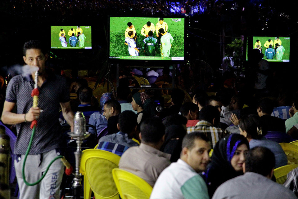 Photo - In this Monday, June 30, 2014 photo, soccer fans watch the World Cup match between Germany and Algeria at a cafe in Cairo, Egypt. Politics and conflict are never far from soccer in the Middle East, but this year's World Cup has been entangled with unprecedented sectarian violence and soaring tensions between Arab countries, pushing fans to watch matches in secret or even on a channel owned by region's number one enemy _ Israel. (AP Photo/Ahmed Abd El Latif, El Shorouk Newspaper) EGYPT OUT