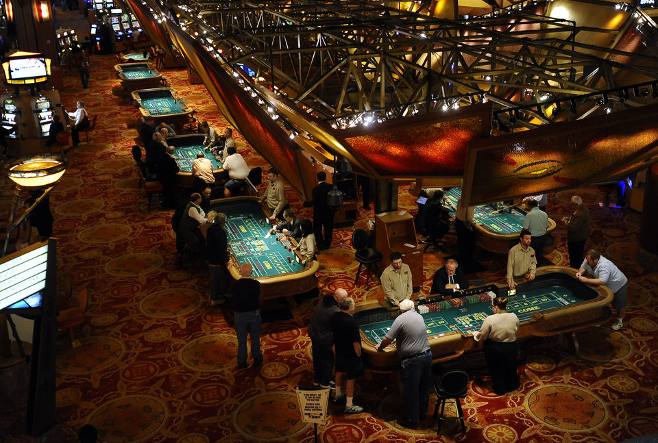 In this Sept. 18, 2013 photo, patrons play craps at tables at Mohegan Sun in Uncasville, Conn. As table games spread across the Northeast, resorts are using their own intelligence network more than ever to stay ahead of suspect players _ professional thieves as well as card counters _ who can easily hit multiple casinos in the span of a few days. (AP Photo/Jessica Hill)