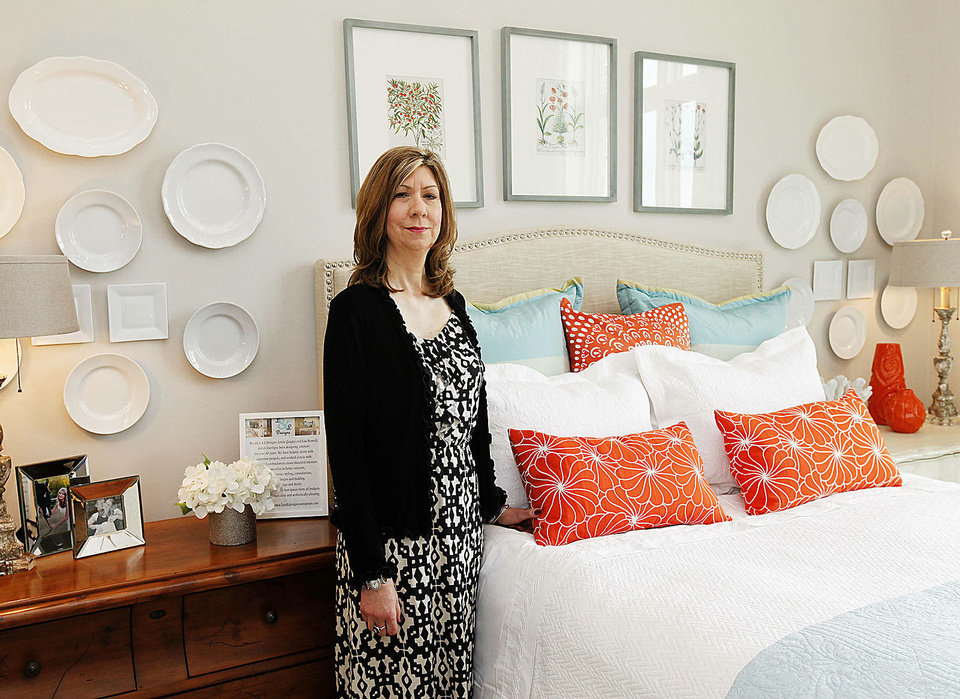 Photo - Cindy Raby, president of the Oklahoma City Orchestra League, shows a bedroom at 1501 NW 158, one of three new homes in this year's Symphony Show House fundraiser.  PAUL HELLSTERN - The Oklahoman