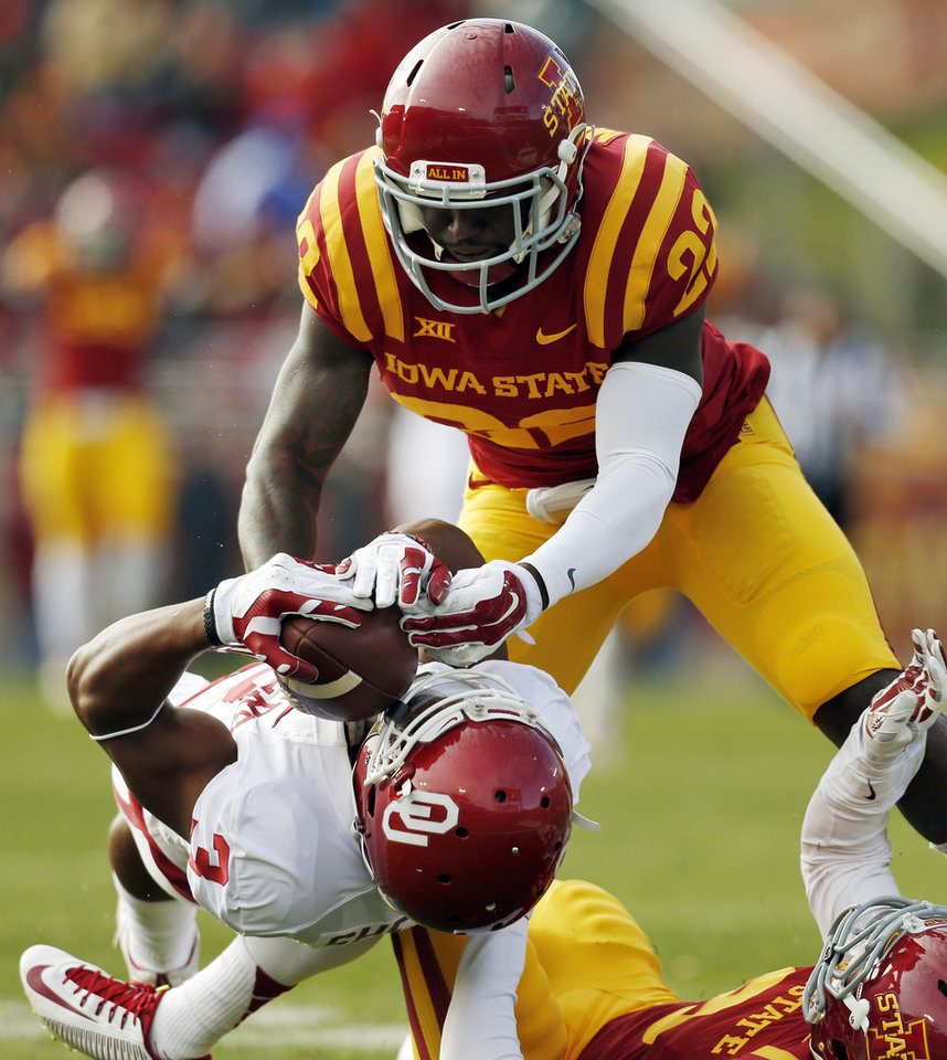 Photo - Oklahoma's Sterling Shepard (3) makes a catch between Iowa State's T.J. Mutcherson (22) and Kenneth Lynn (8) in the first quarter during a college football game between the University of Oklahoma Sooners (OU) and the Iowa State Cyclones (ISU) at Jack Trice Stadium in Ames, Iowa, Saturday, Nov. 1, 2014. Shepard was inured on the play. Photo by Nate Billings, The Oklahoman