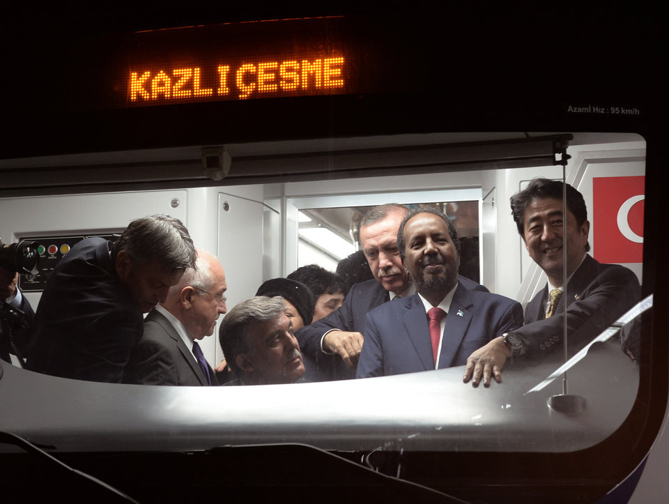 Photo - Japanese Prime Minister Shinzo Abe, right, his Turkish counterpart Recep Tayyip Erdogan, third right, Turkey's President Abdullah Gul, third left, and Somalia's President Hassan Sheikh Mohamud, second right, wait inside a train to cross the Bosporus after the inauguration of the tunnel called  Marmaray in Istanbul, Turkey, Tuesday, Oct. 29, 2013. Turkey is for the first time connecting its European and Asian sides with a railway tunnel set to open Tuesday, completing a plan initially proposed by an Ottoman sultan about 150 years ago. The  Marmaray, is among a number of large infrastructure projects under the government of Prime Minister Recep Tayyip Erdogan that have helped boost the economy but also have provoked a backlash of public protest.(AP Photo)