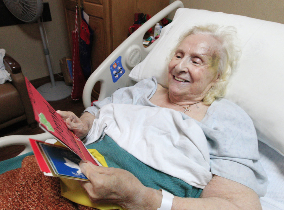 Photo - World War II veteran Peggy Honaker, of Prices Fork, Va., looks at  Christmas cards given to her through the Holiday Mail for Heroes program and delivered  to veterans at the VA Medical Center   in Oklahoma City.  Photo by Paul B. Southerland, The Oklahoman  PAUL B. SOUTHERLAND - PAUL B. SOUTHERLAND
