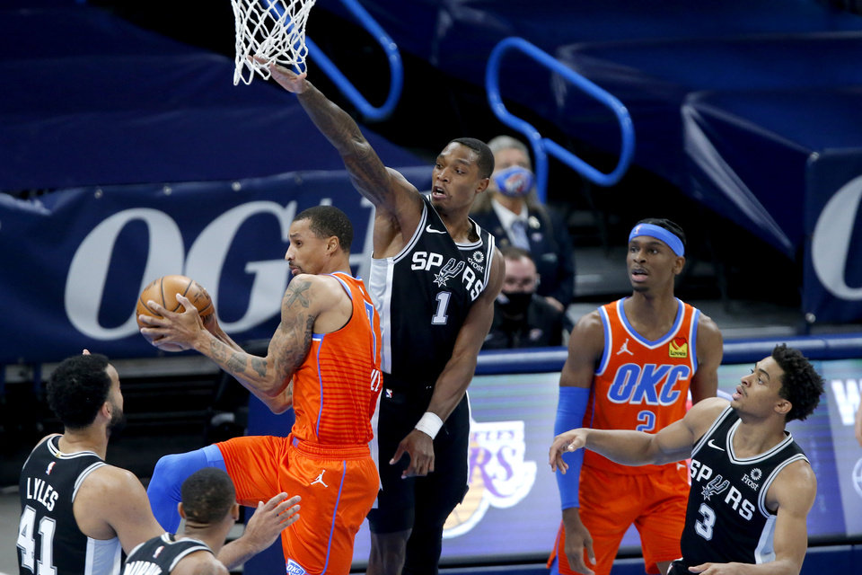 Photo - Oklahoma City's George Hill (3) passes the ball as he goes by San Antonio's Lonnie Walker IV (1) during an NBA basketball game between the Oklahoma City Thunder and the San Antonio Spurs at Chesapeake Energy Arena in Oklahoma City, Tuesday, Jan. 12, 2021. [Bryan Terry/The Oklahoman]
