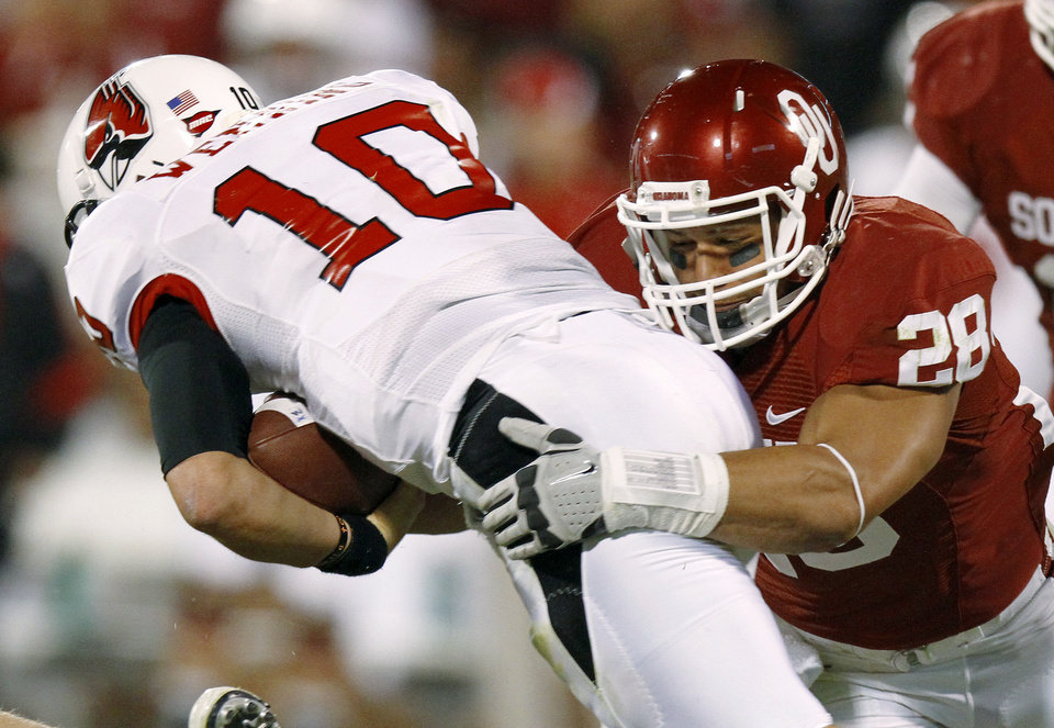 Photo - Oklahoma's Travis Lewis (28) hits Ball State's Keith Wenning (10) causing a fumble during the college football game between the University of Oklahoma Sooners (OU) and the Ball State Cardinals at Gaylord Family-Memorial Stadium on Saturday, Oct. 01, 2011, in Norman, Okla. Photo by Bryan Terry, The Oklahoman