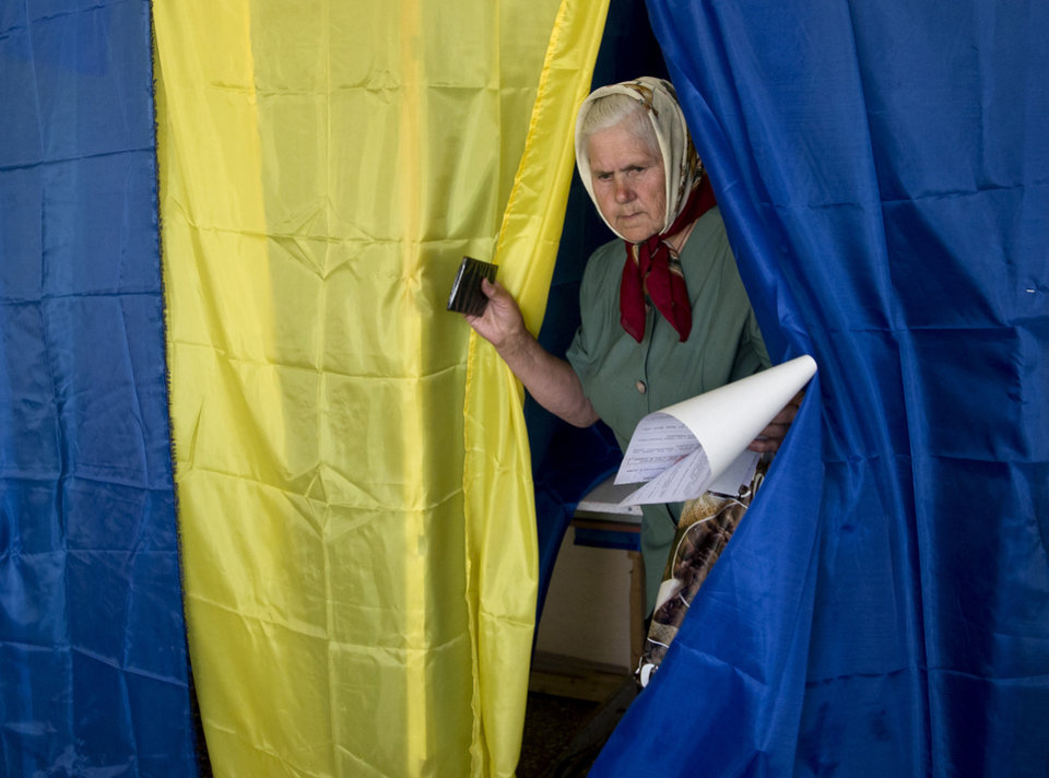 Photo - An elderly woman exits a voting booth after casting her vote in the presidential elections in the eastern town of Krasnoarmiisk, Ukraine, Sunday, May 25, 2014. Ukraine's critical presidential election got underway Sunday under the wary scrutiny of a world eager for stability in a country rocked by a deadly uprising in the east. While there were no immediate reports of violence, pro-Russia insurgents were trying to block voting by snatching ballot boxes and patrolling polling stations. (AP Photo/Vadim Ghirda)